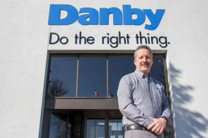 Jim Estill in front of Danby Appliances Sign