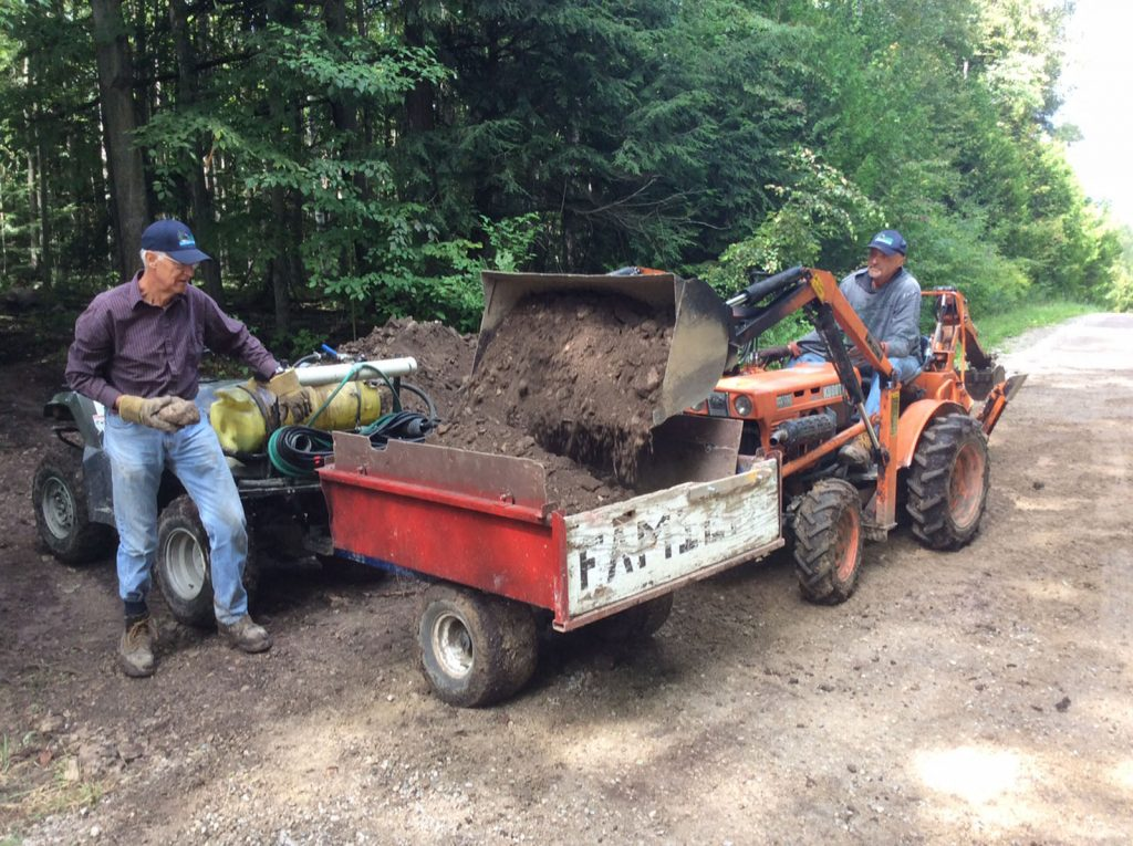 Two men show off the dirt they gathering while making the new Canada 150 trail