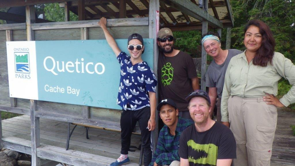 Staff at Quetico Provincial Park stand with the sign