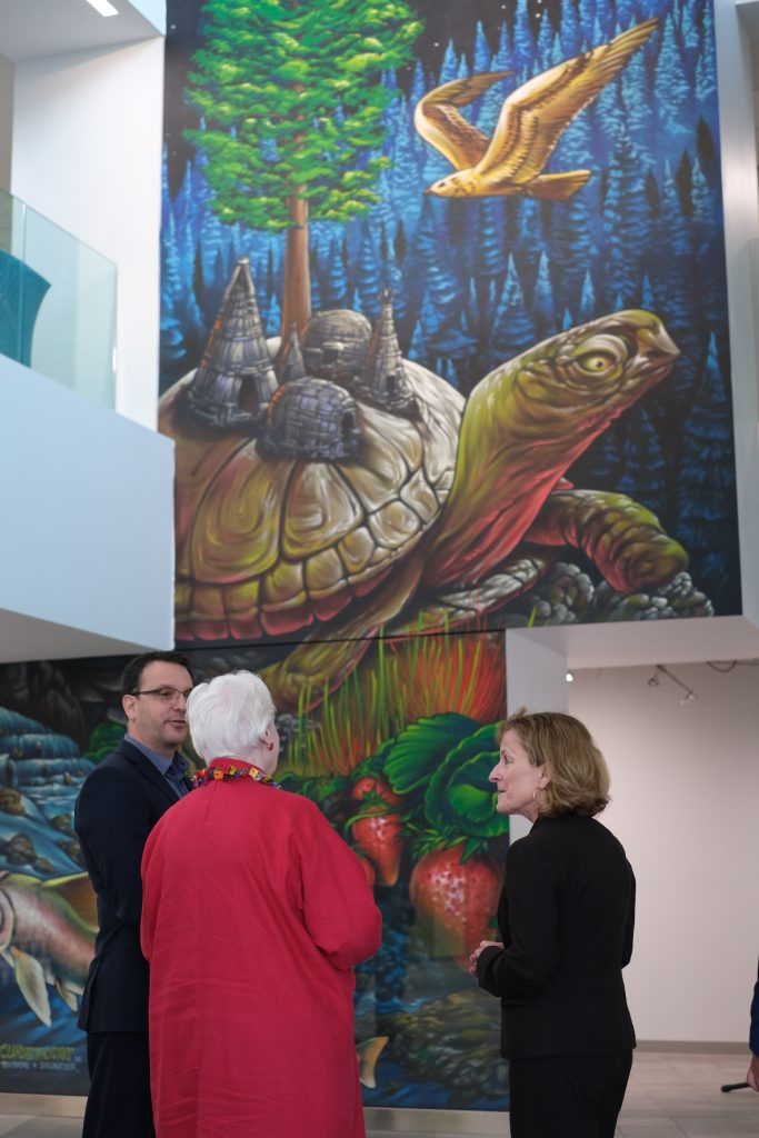 The Lieutenant Governor stands with Alqonquin College in front of an Indigenous mural of Turtle Island