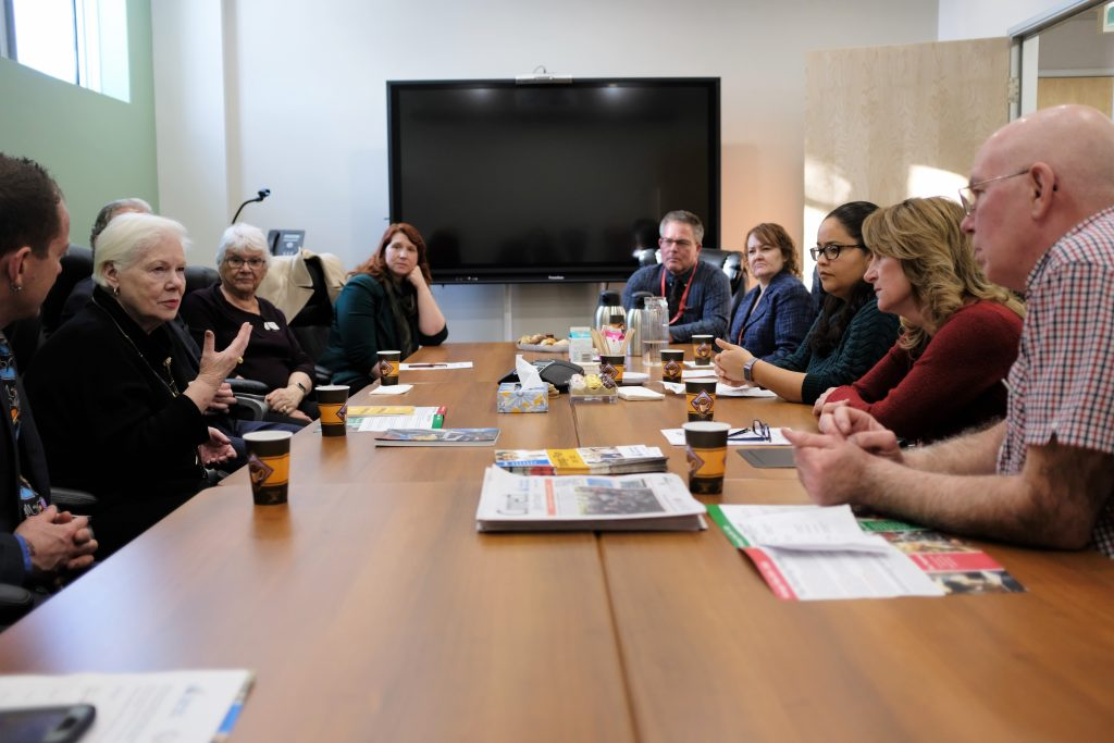 The Lieutenant Governor sits at a board room table with staff of the Thunder Bay Public Library