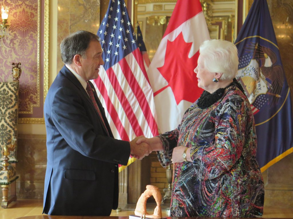 The Lieutenant Governor stands in front of the American and Canadian flags shaking hands with Governor Gary Herbert while visiting the Utah State Capitol building