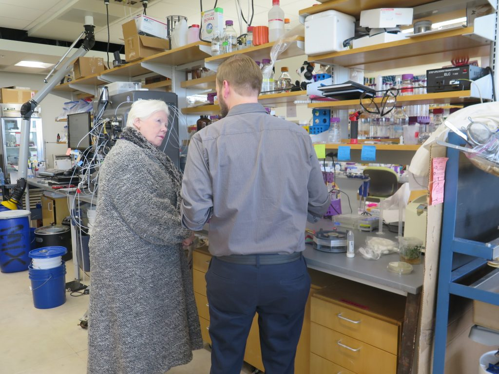 The Lieutenant Governor stands at a lab desk with scientist from the Synthetic Spider Silk Lab at Utah State University