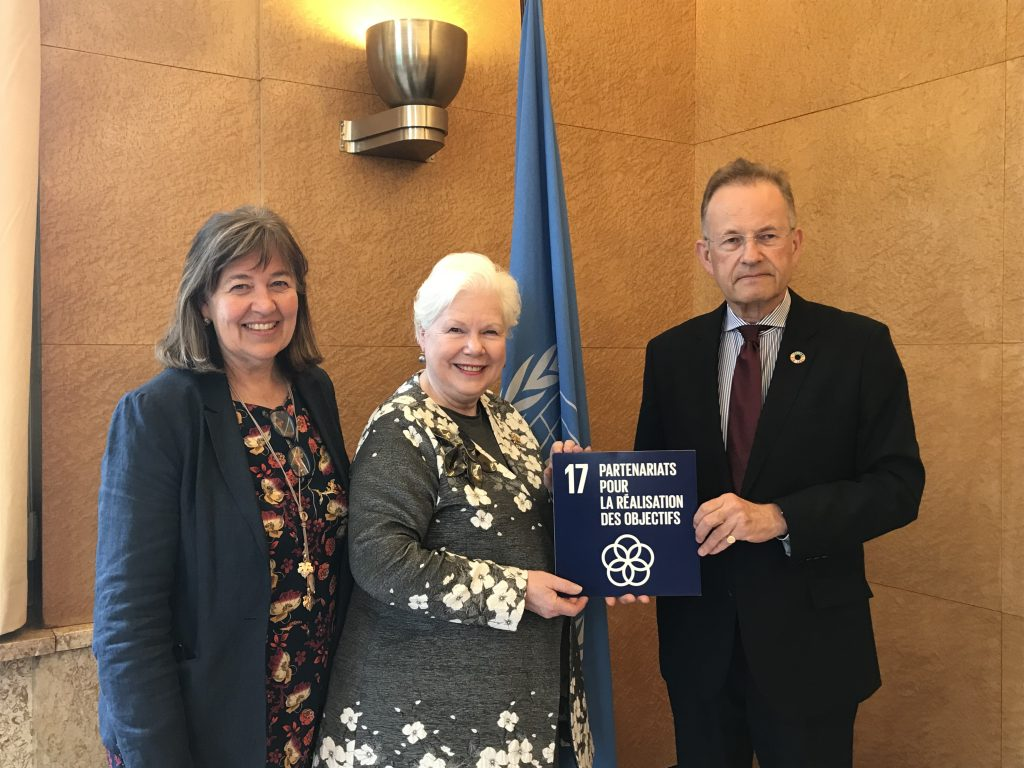 The Lieutenant Governor stands with two United Nations employees holding a dark blue SDG card titled SDG 17 Partnerships for the Goals