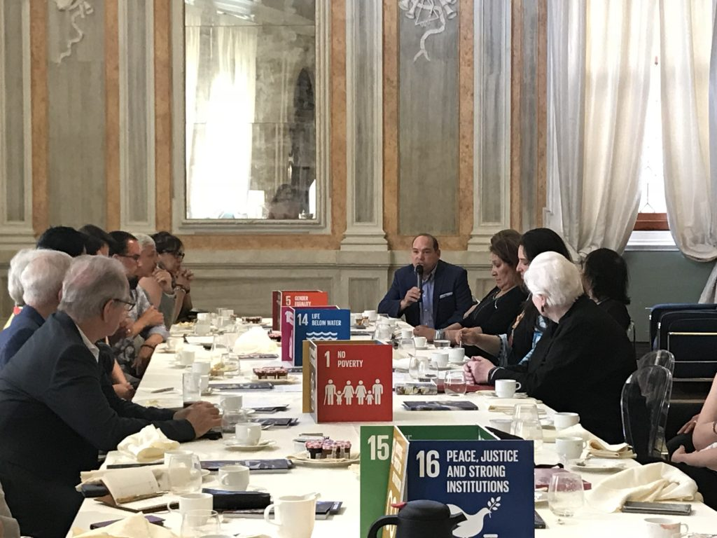 A long table with the colourful SDG cards displayed down the centre around which sit many Canadian architects in conversation with the Lieutenant Governor of Ontario