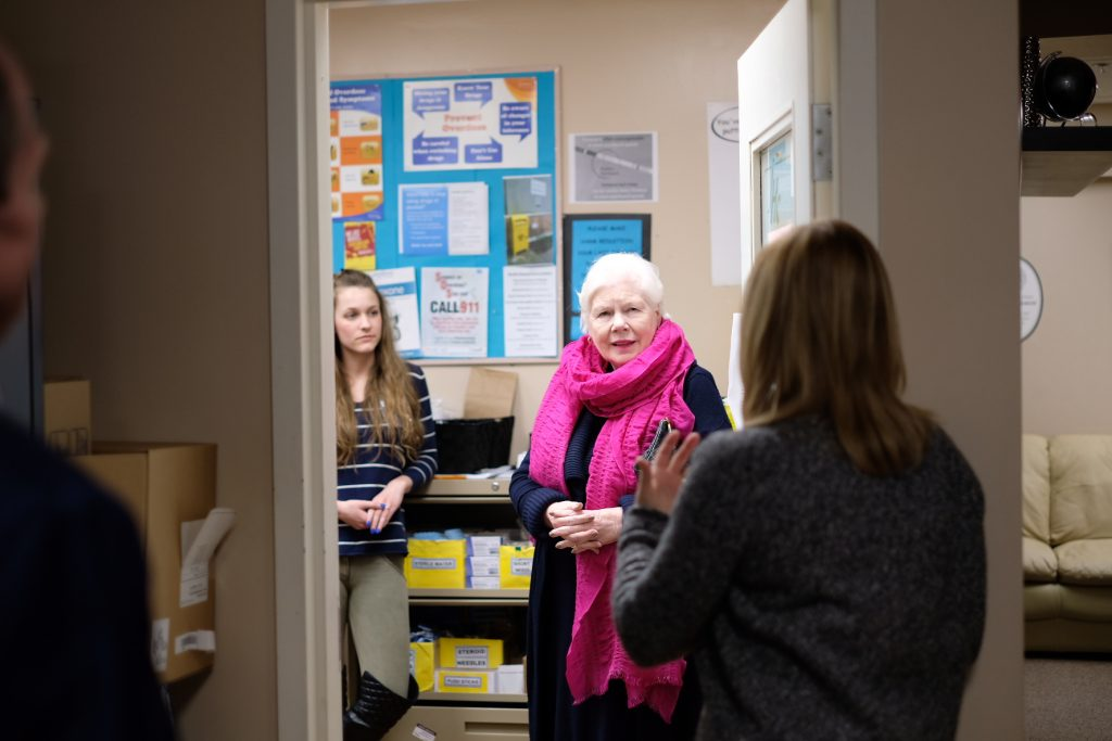 The Lieutenant Governor stands in her scarf and coat in a hallway at the John Howard Society in Oshawa speaking with a staff member who has her back to the camera