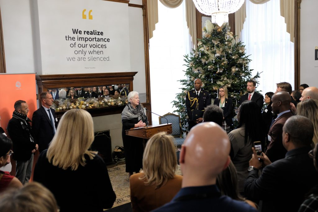 The Lieutenant Governor stands a podium giving remarks to a large grouping of Ontario Public Servants who are facing her. A large Christmas tree is to her right.