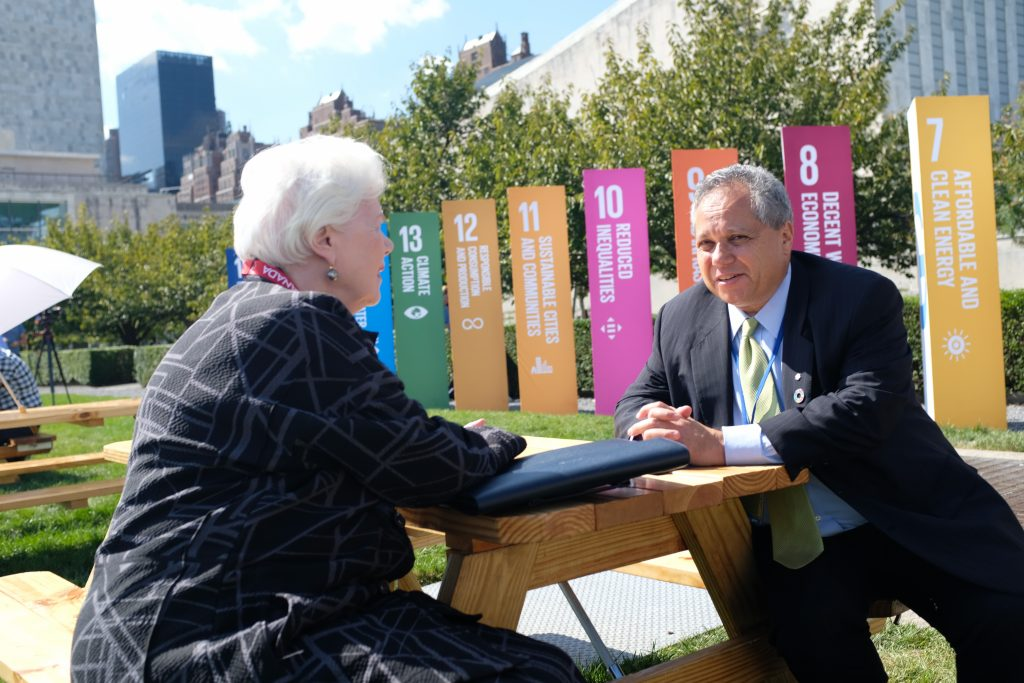 The Lieutenant Governor and Dr. Peter Singer sit at a picnic table with the SDGs in the background