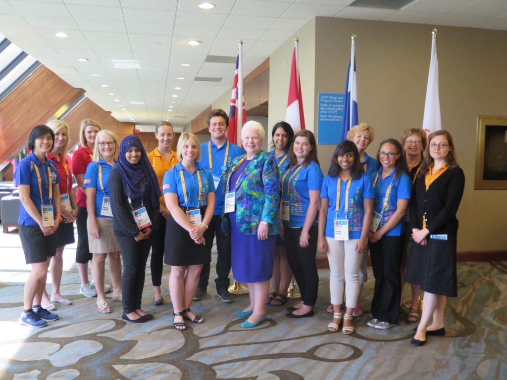 Her Honour stands in a hotel lobby surrounded by Pan Am Protocol staff posing for a photograph