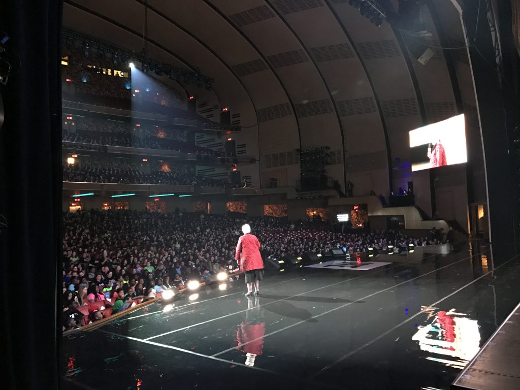 A photo taken from backstage of the Lieutenant Governor in a red dress speaking to 6000 students at Radio City Music Hall