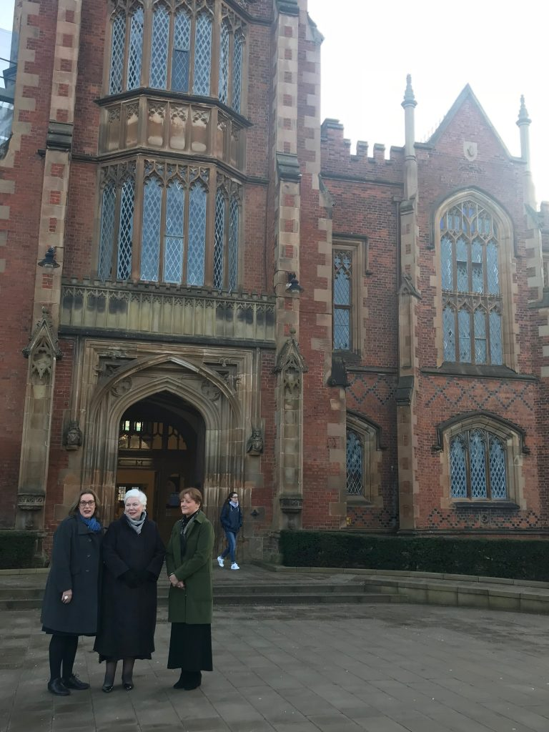 The Lieutenant Governor stands outside a large stone entrance to Queen's University Belfast with two staff