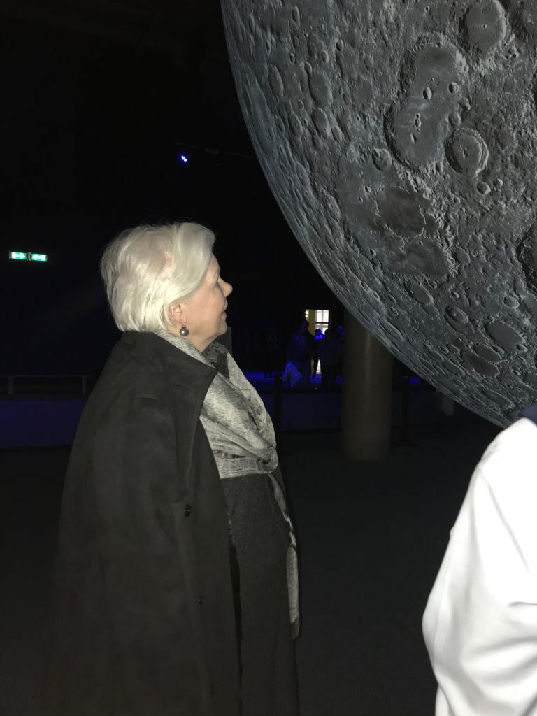 The Lieutenant Governor stands under a large moon installation