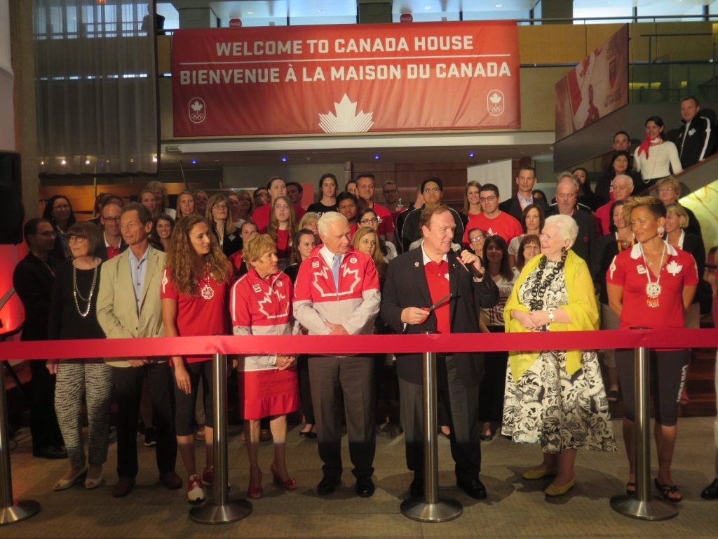 The Lieutenant Governor stands with a VIP line cutting the red ribbon of Canada House