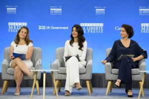Chrystia Freeland and Amal Clooney both dressed in white sit on a stage with a blue media freedom branded background behind them